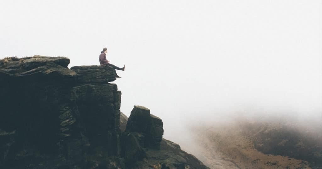 Man sitting on the edge of a cliff holding a phone in his hand