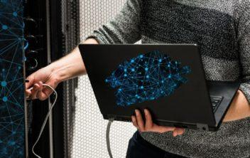 Data center speciliasts plugging computer in